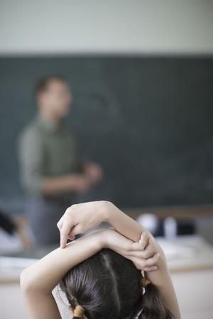 hesitations: School girl raising hands in class