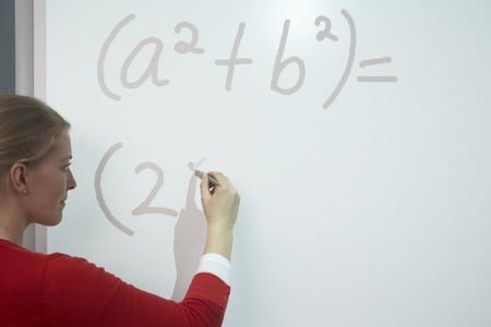 formulae: Teacher writing on whiteboard