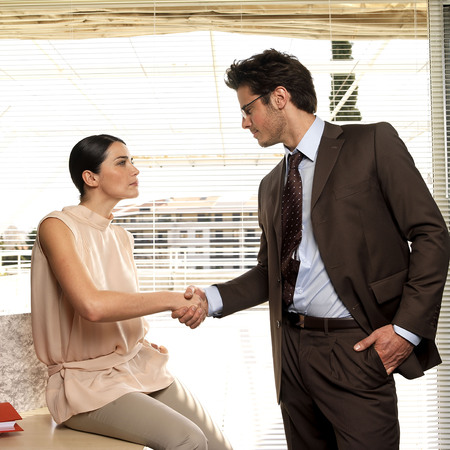 gather: Couple shaking hands in office
