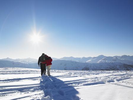 Paare, die in Schnee auf die Gebirgsoberseite gehen