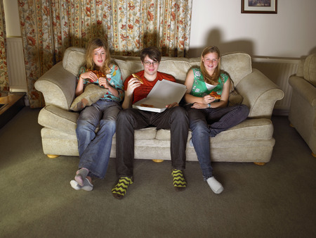 viewed: Females and male on sofa, eating pizza