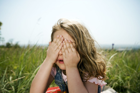 bashfulness: Girl hiding behind hands