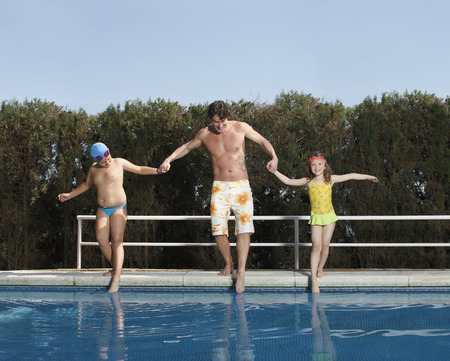 Father and children dipping toes in pool