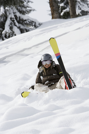Woman sitting in the snow with skis LANG_EVOIMAGES
