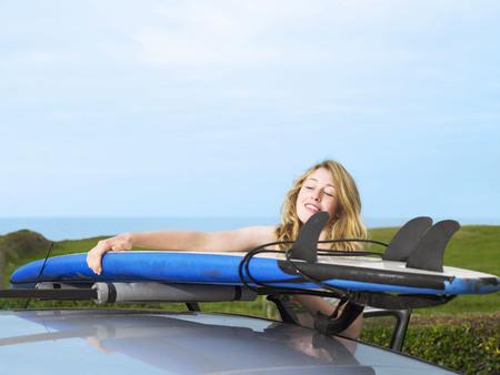 Female taking surfboard off car roof LANG_EVOIMAGES