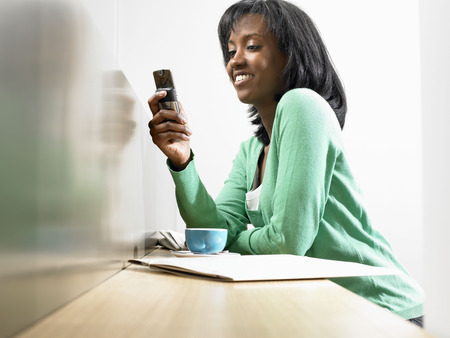 worktops: Woman with coffee, looking at her phone LANG_EVOIMAGES