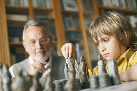 generation gap: Young boy playing chess with grandfather