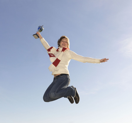 prideful: Woman jumping, holding trophy