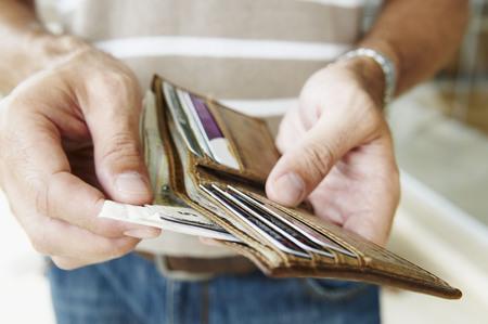 Man removes cash from wallet LANG_EVOIMAGES