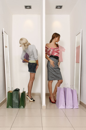 decide deciding: Young women looking at shop mirrors