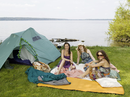 easygoing: Three women camping by the water LANG_EVOIMAGES