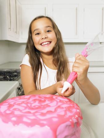 Girl (8-10) icing cake LANG_EVOIMAGES