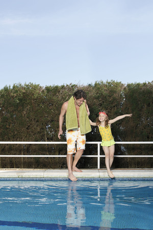 Father and girl dipping toes in pool