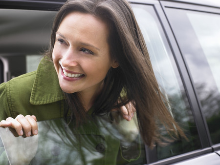 refreshed: Woman passing her head out of the car LANG_EVOIMAGES