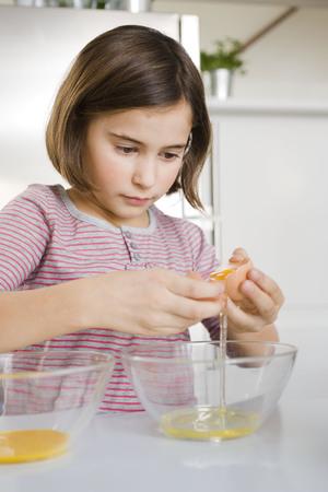 Girl separating egg yolk and egg white LANG_EVOIMAGES