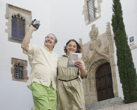 retirees: Retirees taking video and looking at map LANG_EVOIMAGES