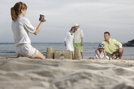Mother taking video of family on beach