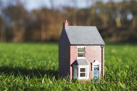 accountable: Model of house sits on lawn