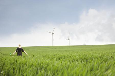 accountable: Pregnant woman walking through wind farm