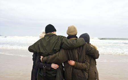 gals: Group of friends hugging on beach LANG_EVOIMAGES