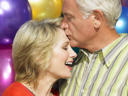 smooching: Senior couple embracing LANG_EVOIMAGES