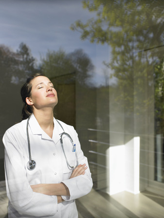 liable: Young female doctor by the window LANG_EVOIMAGES
