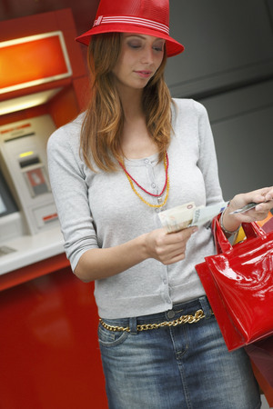 withdrawing: Young woman withdrawing cash