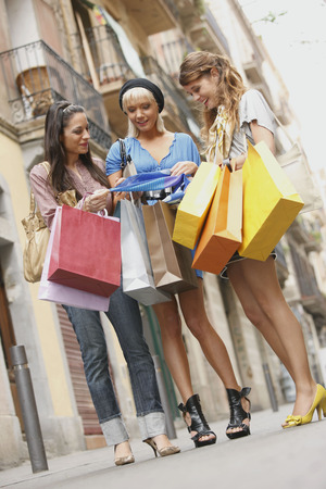 buying time: Young women walking with shopping bags LANG_EVOIMAGES