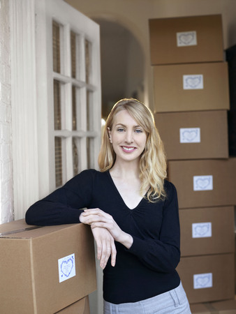 Woman leaning on boxes in doorway