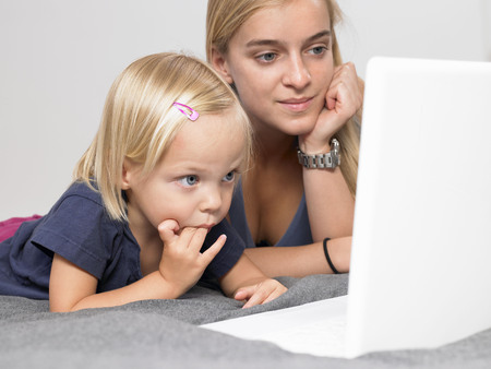 captivation: Daughter and mother looking at a laptop