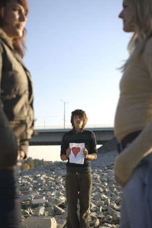 bashfulness: Boy holding paper heart looking at girl LANG_EVOIMAGES