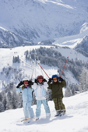 mischievious: Group of kids standing in snow with skis