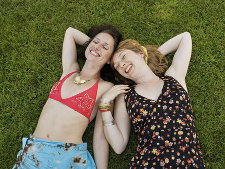 Two women laying on grass smiling