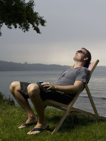 stormy waters: Man sitting in garden chair outdoors
