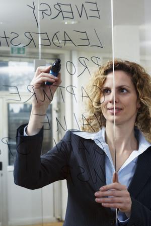 accomplishes: Businesswoman writing keywords on glass