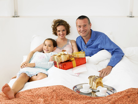 womens hands: Girl on bed with mother and father LANG_EVOIMAGES