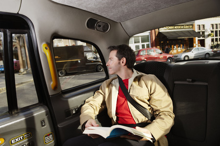 taxicabs: Man looking out of taxi window LANG_EVOIMAGES