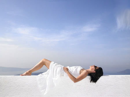 sightseers: Woman resting on a white wall
