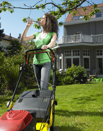 uncomplicated: Woman mowing lawn in the sun