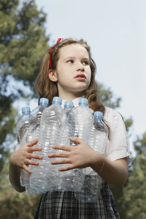 Young girl holding empty bottles