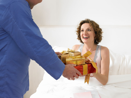 Man handing woman presents in bed