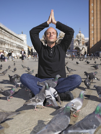 sightseers: Man doing yoga, surrounded by pigeons