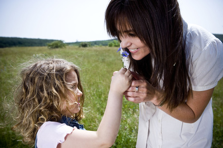 uncomplicated: Woman smelling flower with daughter