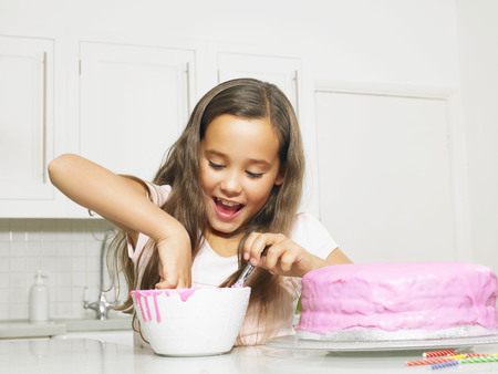 rejoices: Girl (8-10) dipping finger in icing bowl