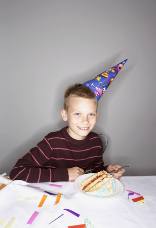 grays: Boy (8-10) with slice of birthday cake LANG_EVOIMAGES