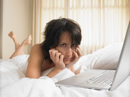 teleworking: Woman in bed with computer LANG_EVOIMAGES