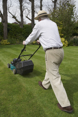 advances: Man mows garden lawn LANG_EVOIMAGES