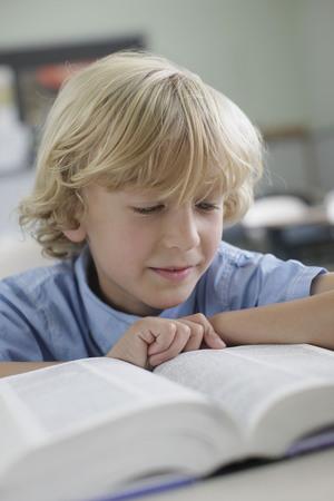 studied: School boy reading book in class