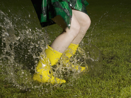 rejuvenated: Woman jumping in rain puddle