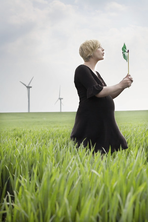 Pregnant woman blowing a windmill LANG_EVOIMAGES